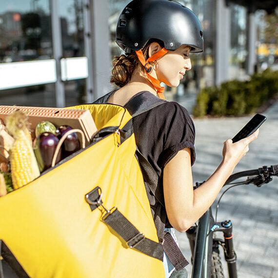 Junge FRau mit Fahrrad uhnd Lebensmitteln im Rucksack
